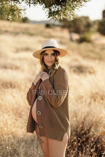 Cheerful pregnant woman wearing a hat lingerie and cardigan standing among dry grass in field placed in countryside and looking at camera in sunny day — Stock Photo