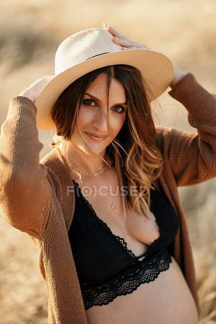 Pensive femme enceinte en lingerie et cardigan debout parmi l'herbe sèche dans le champ placé à la campagne et en regardant la caméra dans la journée ensoleillée — Photo de stock