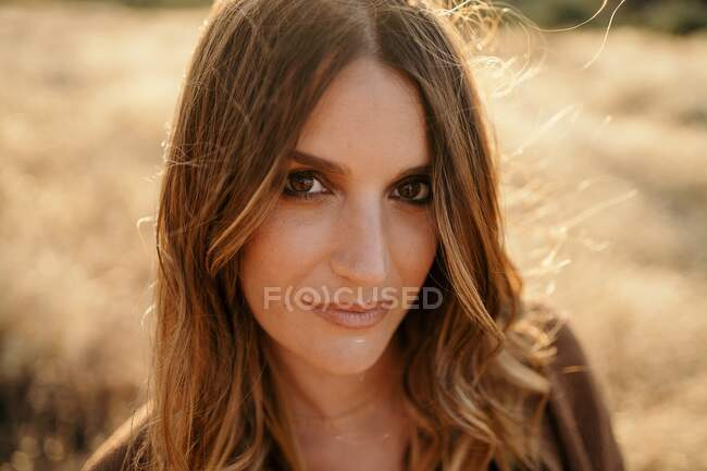 Portrait of confident woman standing in field with dry grass in sunny day and looking at camera — Stock Photo