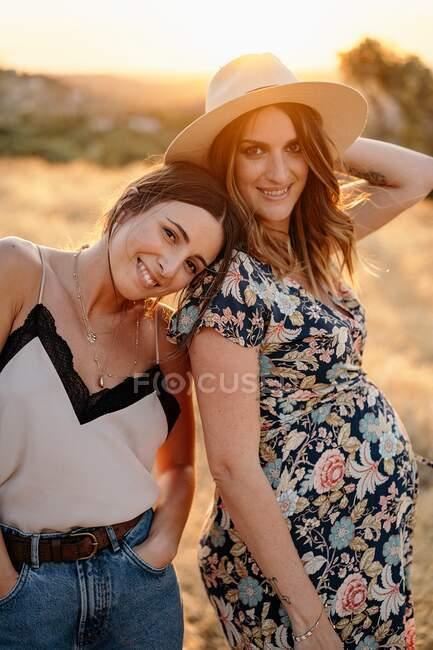 Очаровательная женщина в модном наряде опирается головой на положительную беременную женщину, стоя в поле в сельской местности и глядя в камеру в солнечный день — стоковое фото