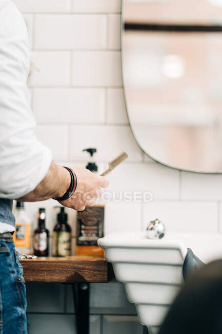 Crop unrecognizable male stylist holding straight razor with sharp blade in beauty salon in daytime — Stock Photo