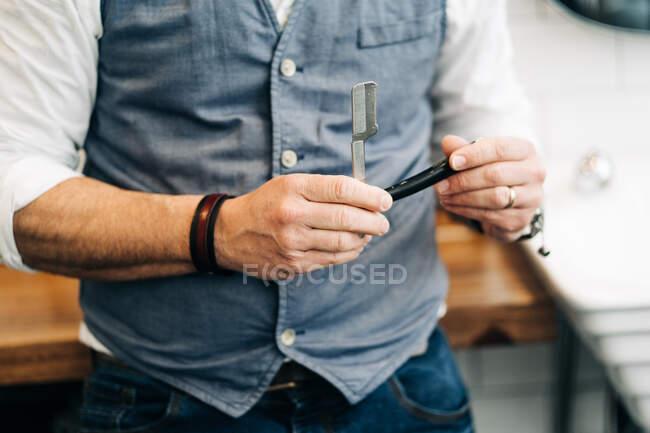 Нерозпізнаний чоловічий стиліст, який тримає пряму бритву з гострим лезом у салоні краси вдень. — стокове фото