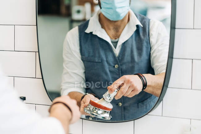 Crop anonymous male beauty master in sterile mask preparing shave brush with soap in bowl against mirror in bathroom at work - foto de stock