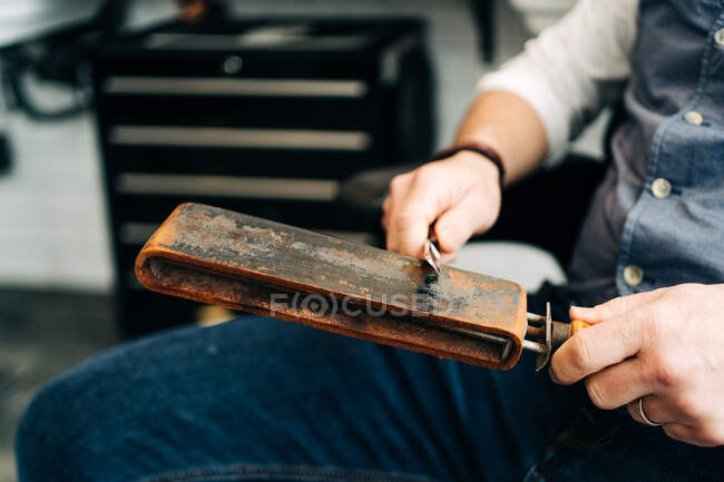 Cropped unrecognizable male barber with razor and sharpening stropping leather classic tool — Stockfoto
