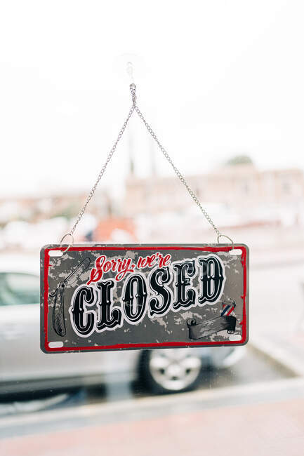 Rectangular shaped signboard with Sorry and Closed titles hanging on transparent wall in city — Photo de stock