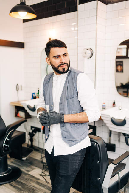 Self assured adult bearded male hairstylist in waistcoat looking away standing in barbershop holding tools — Stock Photo