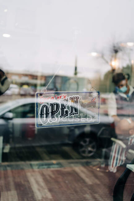 Rectangular shaped signboard with Come in we are Open titles hanging on transparent wall door of shop - foto de stock