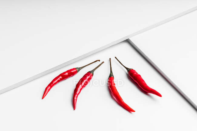 High angle composition of hot red chili peppers arranged plate against white geometric surface background — Stock Photo