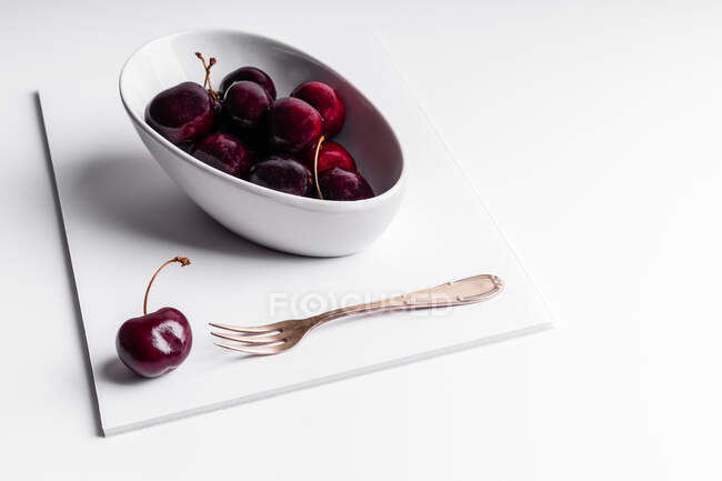 High angle of healthy ripe tasty cherries in ceramic bowl placed on white board — Stock Photo