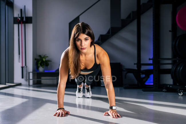 Full body of concentrated sportswoman standing in plank position while training abs  muscles in modern fitness center - foto de stock