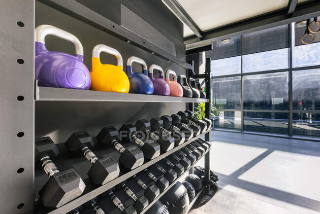 Interior of modern gym with kettlebells and wall balls with battle rope on rack near shelving with sports nutrition — стоковое фото