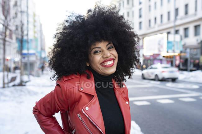 Чорна жінка з волоссям афро на вулиці і посміхається перед камерою. — стокове фото