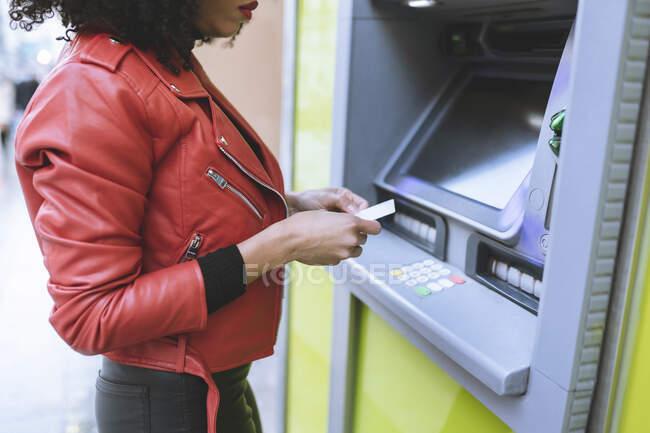 Femme afro-américaine anonyme se tenant près d'un distributeur automatique et insérant une carte de crédit tout en souriant largement et en détournant les yeux — Photo de stock