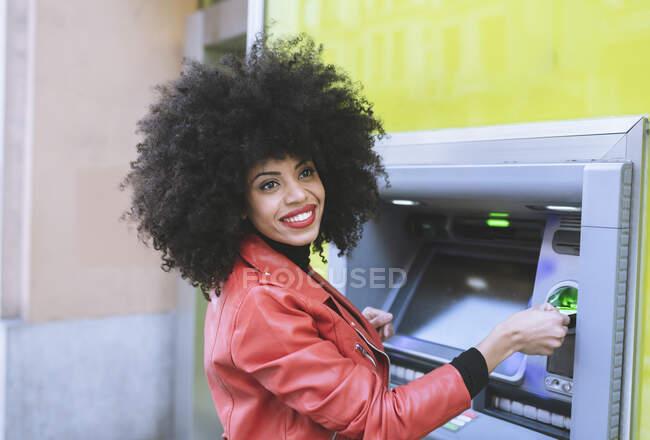 Vue latérale d'une femme afro-américaine positive se tenant près d'un distributeur automatique et insérant une carte de crédit tout en souriant largement et en détournant les yeux — Photo de stock