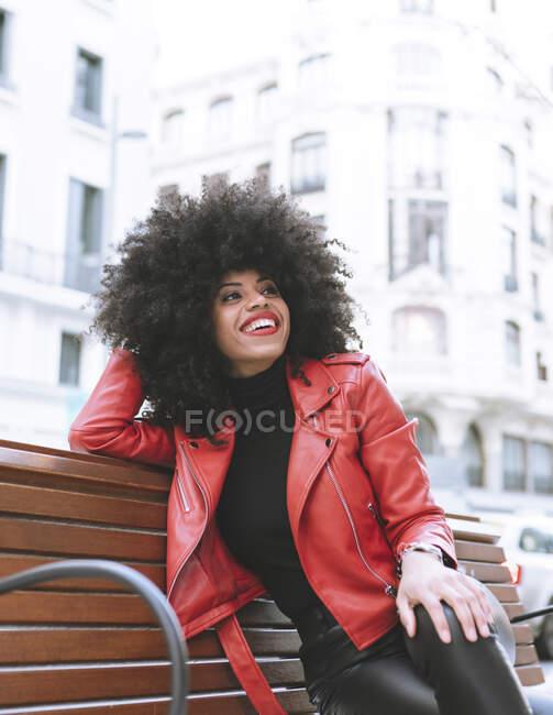 Bajo ángulo de alegre hembra afroamericana con peinado afro apoyado en la mano sentado con las piernas cruzadas en el banco y mirando hacia otro lado - foto de stock