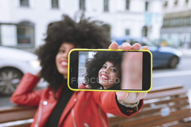 Selective focus of glad African American female with Afro hairstyle sitting on bench and taking self portrait on cellphone — Stock Photo