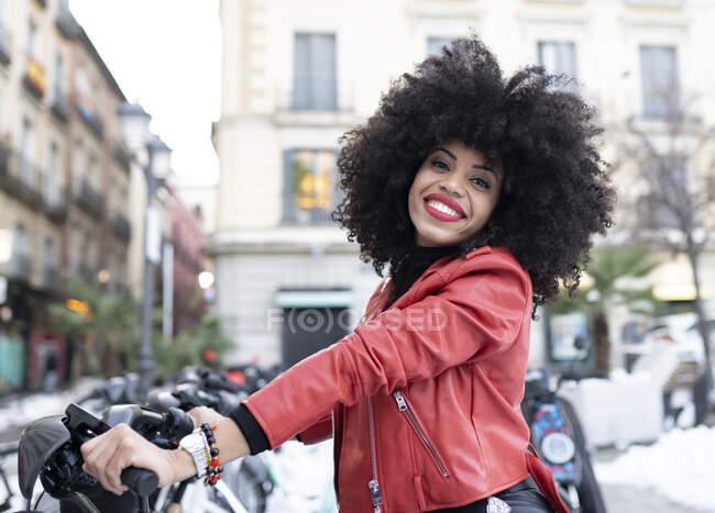 Бічний погляд на позитивну афро-американську жінку з кучерявим волоссям стоїть з велосипедом і дивиться на камеру — стокове фото