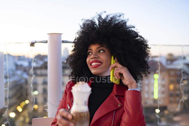 Femme afro-américaine joyeuse avec une coiffure afro souriante tout en étant assise sur le balcon avec un verre de boisson et en parlant sur un téléphone portable — Photo de stock
