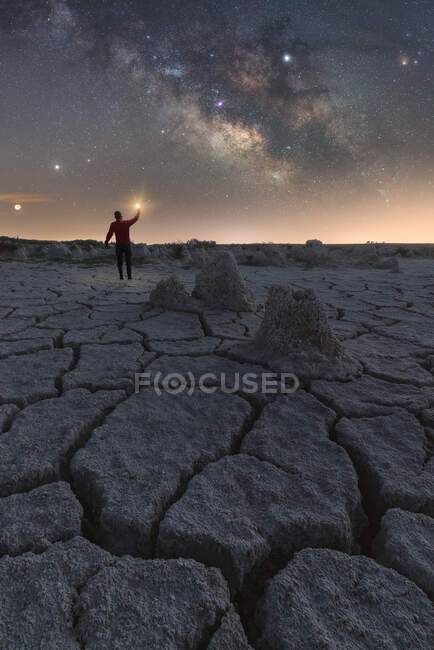 Tourist standing in rocky arid terrain with flashlight under starry sky at night — Stock Photo