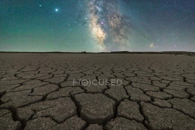 Drought cracked lifeless ground arid terrain with starry sky at night — Stock Photo