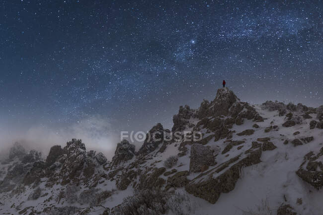 Traveler with glowing flashlight standing on cliff of mountain range in Picos de Europa National Park under dark starry night sky — Stock Photo