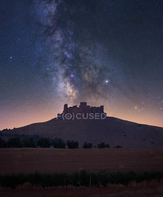Scenery of field against Almonacid castle on hilltop under shining stars on dark night sky — Stock Photo