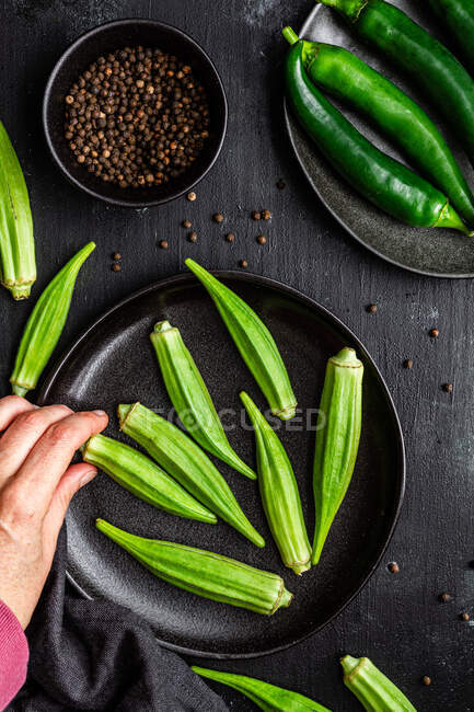 Crop unrecognizable person holding ripe okra over table with fresh vegetables on frying pan — Stock Photo