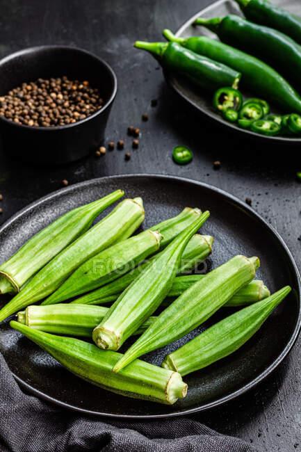 Vista superior de superalimentos verdes maduros en platos negros de cerámica cerca de pimienta en un tazón en la mesa - foto de stock