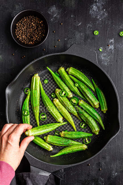 From above crop unrecognizable person holding ripe okra over table with fresh vegetables on frying pan — Stock Photo