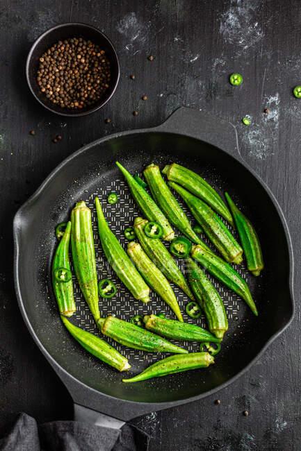 De arriba rasgó okra fresca en la sartén con pimienta verde sobre fondo oscuro - foto de stock