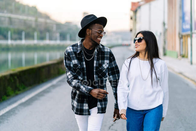 Young content multiracial partners in trendy clothes and sunglasses talking while looking at each other and strolling on city roadway — Stock Photo
