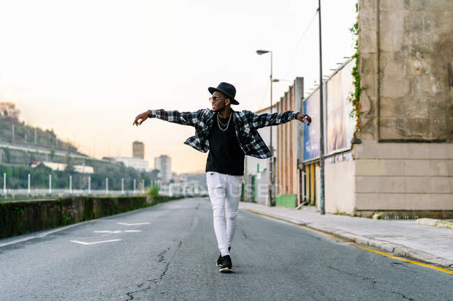 Young African American male in trendy wear and chain looking away on urban asphalt roadway — стоковое фото