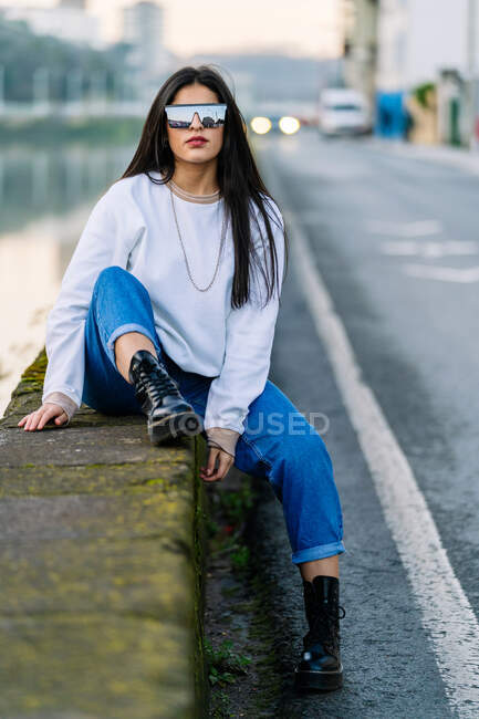 Young brunette in trendy wear and boots resting on rough fence between urban roadway and river in daylight — Stock Photo