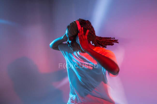 Chica adolescente afroamericana seria en auriculares bailando en el estudio con luces de neón brillantes - foto de stock