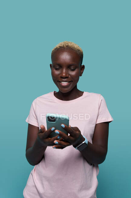 Expressive belle femme afro-américaine aux cheveux courts et à la manucure lumineuse naviguant sur smartphone sur fond bleu — Photo de stock