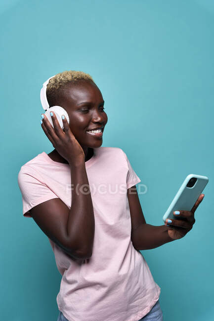 Cheerful African American female toothy smiling with eyes closed while listening to music in headphones against blue background — стоковое фото