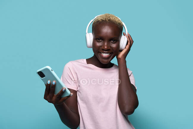 Cheerful African American female toothy smiling looking at camera while listening to music in headphones against blue background - foto de stock