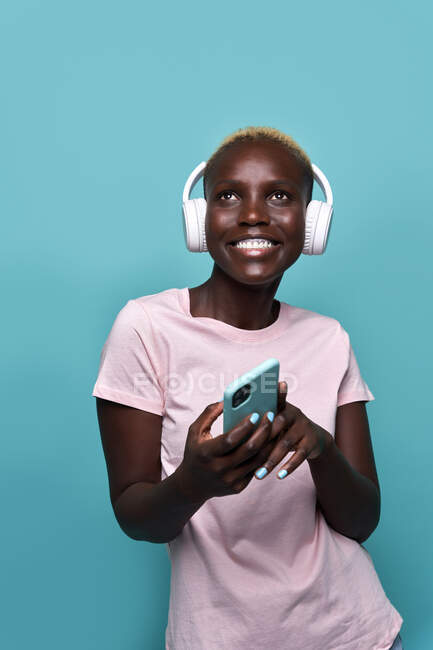 Cheerful African American female toothy smiling while listening to music in headphones against blue background — стоковое фото