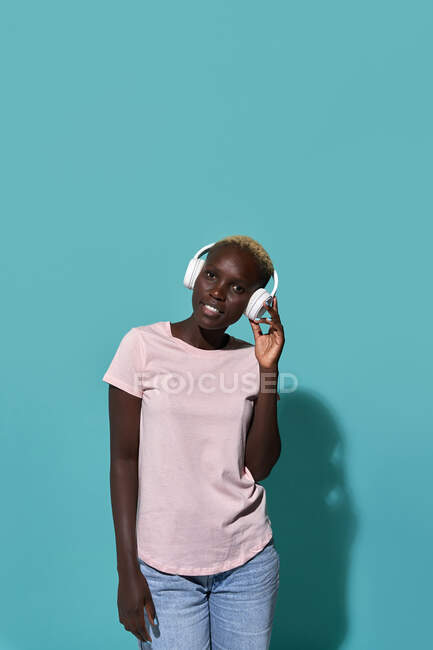 Serene beautiful African American female smiling looking at camera while listening to music in headphones against blue background — Stock Photo