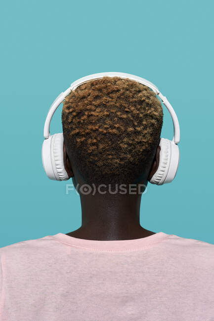 Back view of faceless African American female with short hair listening to music in headphones while standing against blue background — Stock Photo