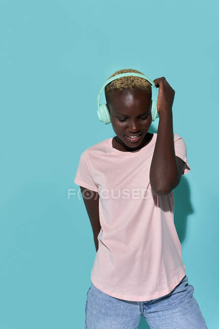 Cheerful African American female toothy smiling with eyes closed listening to music in headphones against blue background — Stock Photo
