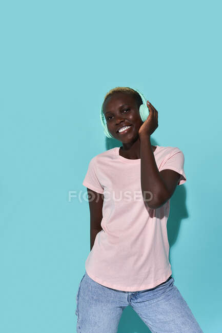 Cheerful African American female toothy smiling looking at camera listening to music in headphones against blue background — Stock Photo