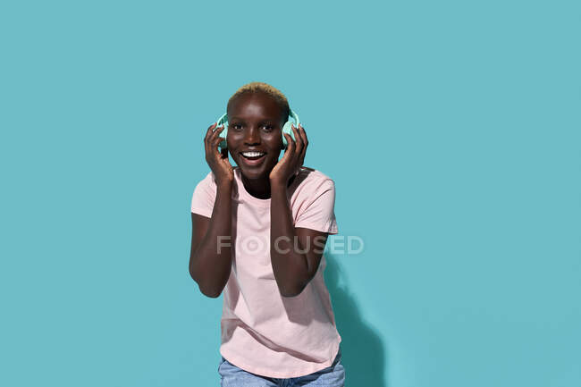 Cheerful African American female toothy smiling looking at camera listening to music in headphones against blue background — стоковое фото