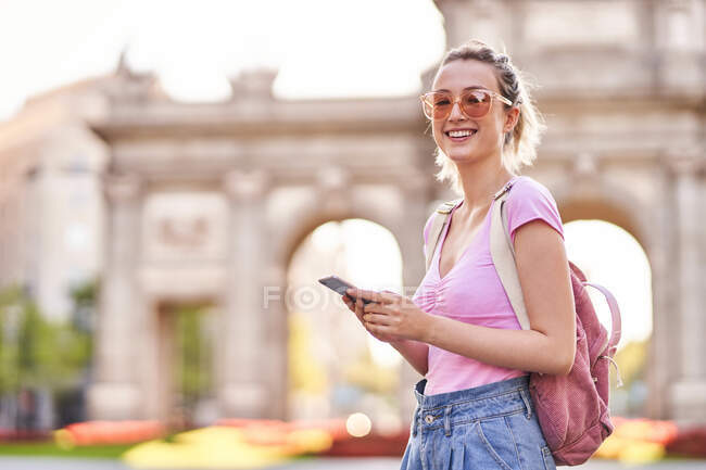 Side view of happy female with backpack browsing mobile phone while exploring Madrid streets — Stock Photo