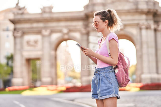 Side view of serious female with backpack browsing mobile phone while exploring Madrid streets — Foto stock