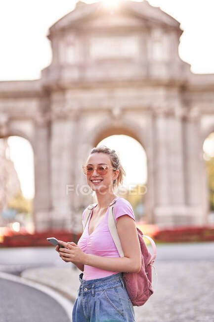 Side view of happy female with backpack browsing mobile phone while exploring Madrid streets — Foto stock