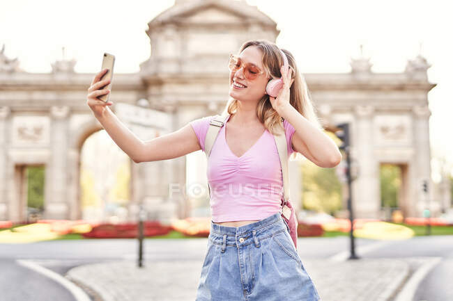 Cheerful female in casual outfit and sunglasses taking self portrait while listening to music on Madrid street — Foto stock