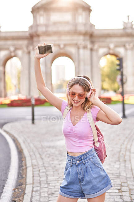 Cheerful female in casual outfit and sunglasses listen to music on Madrid street — Foto stock
