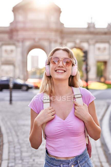Felice femmina in piedi sotto il sole durante il viaggio a Madrid e guardando la fotocamera — Foto stock