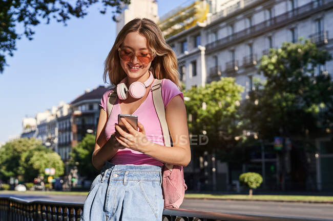 Cheerful woman browsing mobile phone while leaning on handrail on sidewalk on street of Madrid — Stock Photo